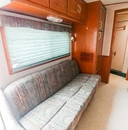 View of the Sofa in a 1999 Sundowner Horse Trailer at Luxury Coach