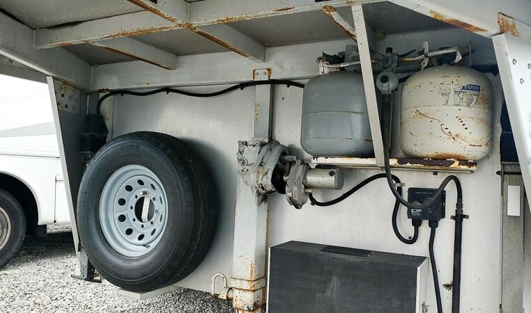 View of the LP Tanks and Spare Tire in a 1999 Sundowner Horse Trailer at Luxury Coach
